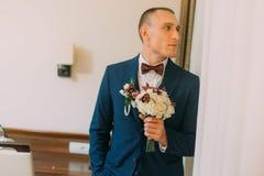 Μοντέρνο ντυμένο άτομο που κρατά την κομψή floral ανθοδέσμη στεμένος κοντά στον τοίχο του δωματίου ξενοδοχείου Στοκ εικόνα με δικαίωμα ελεύθερης χρήσης