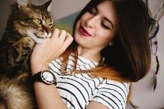 Μοντέρνο παιχνίδι γυναικών hipster με τη γάτα της στο σύγχρονο δωμάτιο στοκ εικόνες