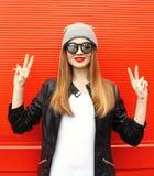 Μοντέρνο δροσερό κορίτσι μόδας που έχει τη διασκέδαση που φορά ένα μαύρο σακάκι και τα γυαλιά ηλίου δέρματος βράχου με το καπέλο Στοκ Φωτογραφία