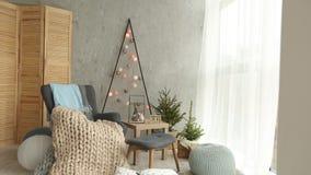 Μοντέρνο Σκανδιναβικό εσωτερικό Χριστουγέννων με μια κομψή πολυθρόνα και ένα θερμό καρό merinos Σπίτι άνεσης με σκανδιναβικό νέο απόθεμα βίντεο