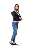 Μοντέρνο σύγχρονο κορίτσι μόδας στα τζιν και το σακάκι δέρματος που κοιτάζει πίσω από πέρα από τον ώμο Στοκ Φωτογραφία
