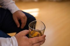 Μοντέρνο χέρι ατόμων ` s με και ένα ποτήρι του ουίσκυ στο χέρι του Ένα ποτήρι του ουίσκυ σε ένα χέρι groom's Στοκ Εικόνα