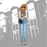 Μοντέρνο χαριτωμένο κορίτσι σε ένα σακάκι, το παντελόνι τζιν παντελόνι, τα γυαλιά ηλίου και τις μπότες αστραγάλων απεικόνιση αποθεμάτων