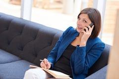 Μοντέρνο busineswoman να ανατρέξει μιλώντας στο τηλέφωνό της Στοκ Εικόνες