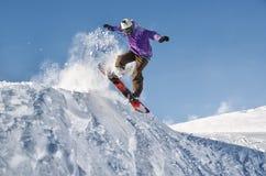 Μοντέρνο snowboarder με τα άλματα κρανών και μασκών από την υψηλή κλίση χιονιού Στοκ Φωτογραφία