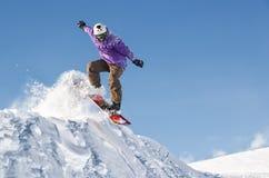 Μοντέρνο snowboarder με τα άλματα κρανών και μασκών από την υψηλή κλίση χιονιού Στοκ εικόνες με δικαίωμα ελεύθερης χρήσης