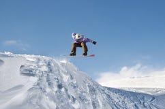 Μοντέρνο snowboarder με τα άλματα κρανών και μασκών από την υψηλή κλίση χιονιού Στοκ φωτογραφία με δικαίωμα ελεύθερης χρήσης