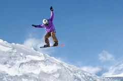Μοντέρνο snowboarder με τα άλματα κρανών και μασκών από την υψηλή κλίση χιονιού Στοκ Εικόνες