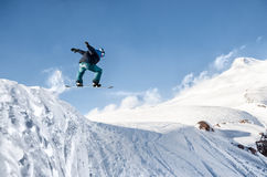 Μοντέρνο snowboarder με τα άλματα κρανών και μασκών από την υψηλή κλίση χιονιού Στοκ εικόνα με δικαίωμα ελεύθερης χρήσης
