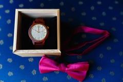 Μοντέρνο wristwatch σε ένα ξύλινο κιβώτιο Ρόδινος δεσμός τόξων Ένα σύνολο των ατόμων εξαρτημάτων σε μια παλαιά ξύλινη καρέκλα με  στοκ εικόνες