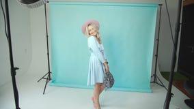 Μοντέλο στο φόρεμα το καπέλο θέτει σε ένα cyclogram και ένα τυρκουάζ υπόβαθρο φιλμ μικρού μήκους