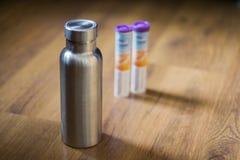 Μονωμένο ανοξείδωτο μπουκάλι δίπλα στις dissolvable ταμπλέτες βιταμινών στοκ εικόνες