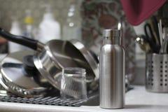 Μονωμένο ανοξείδωτο μπουκάλι με τα εργαλεία και το υπόβαθρο κουζινών νεροχυτών στοκ φωτογραφίες