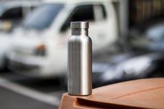 Μονωμένο ανοξείδωτο μπουκάλι με το υπόβαθρο χώρων στάθμευσης στοκ εικόνες
