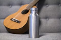 Μονωμένο ανοξείδωτο μπουκάλι με το ukulele σε έναν καναπέ στοκ φωτογραφία με δικαίωμα ελεύθερης χρήσης