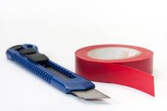 Μονώνοντας ταινία και μπλε χειρουργικό νυστέρι στο άσπρο υπόβαθρο Στοκ εικόνα με δικαίωμα ελεύθερης χρήσης