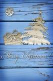 Μορφές συμβόλων Χριστουγέννων που κόβονται από τα φύλλα μουσικής στην μπλε ξύλινη ΤΣΕ Στοκ Εικόνα