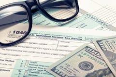 Μορφή αμερικανικού 1040 φόρου με τα γυαλιά και τα δολάρια - πυροβολισμός στούντιο Φιλτραρισμένη εικόνα: επεξεργασμένη σταυρός εκλ Στοκ εικόνα με δικαίωμα ελεύθερης χρήσης