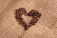 Μορφή καρδιών από τα φυσικά καφετιά ψημένα φασόλια καφέ στοκ φωτογραφία με δικαίωμα ελεύθερης χρήσης