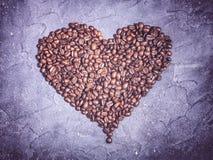 Μορφή καρδιών από τα ψημένα φασόλια καφέ σε ένα ιώδες υπόβαθρο πετρών Στοκ Εικόνες
