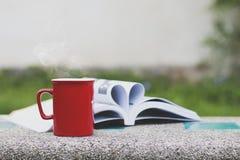 Μορφή καρδιών στο βιβλίο και το φλιτζάνι του καφέ στον πίνακα στοκ φωτογραφία