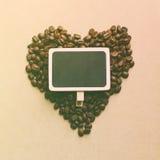 Μορφή καρδιών από τα φασόλια καφέ με τον κενό πίνακα στοκ εικόνες με δικαίωμα ελεύθερης χρήσης