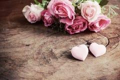 Μορφή καρδιών με το ρόδινο ροδαλό λουλούδι στον ξύλινο πίνακα Στοκ Εικόνες