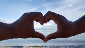 Μορφή καρδιών με το χέρι και στην παραλία Στοκ Φωτογραφία