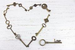 Μορφή καρδιών που γίνεται με τα παλαιά παλαιά κλειδιά ανασκόπησης η μπλε κιβωτίων καρδιά δώρων ημέρας έννοιας εννοιολογική απομόν Στοκ Φωτογραφίες