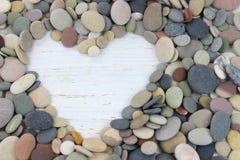 Μορφή καρδιών που γίνεται με τα χαλίκια σε ένα άσπρο στενοχωρημένο ξύλινο backgro Στοκ φωτογραφίες με δικαίωμα ελεύθερης χρήσης