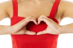 Μορφή καρδιών, σημάδι χειρονομίας χεριών Γυναίκα στο κόκκινο που παρουσιάζει σύμβολο υγείας Στοκ εικόνες με δικαίωμα ελεύθερης χρήσης