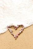 Μορφή καρδιών στα ρόδινα κοχύλια θάλασσας στην παραλία Στοκ εικόνες με δικαίωμα ελεύθερης χρήσης