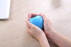 Μορφή καρδιών σφαιρών εκμετάλλευσης χεριών στο ξύλινο γραφείο Στοκ Εικόνα