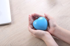 Μορφή καρδιών σφαιρών εκμετάλλευσης χεριών στο ξύλινο γραφείο Στοκ Φωτογραφία