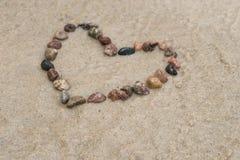 Μορφή καρδιών χαλικιών στην άμμο Στοκ Φωτογραφία