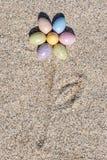 Μορφή λουλουδιών φιαγμένη από ζωηρόχρωμα αυγά Πάσχας στην παραλία ι Στοκ φωτογραφία με δικαίωμα ελεύθερης χρήσης