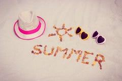 Μορφή του ήλιου και του καλοκαιριού λέξης, γυαλιά ηλίου και καπέλο αχύρου στην άμμο στην παραλία, προστασία ήλιων, θερινός χρόνος Στοκ φωτογραφία με δικαίωμα ελεύθερης χρήσης
