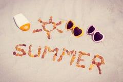 Μορφή του ήλιου και του καλοκαιριού λέξης, γυαλιά ηλίου και λοσιόν ήλιων στην άμμο στην παραλία Στοκ φωτογραφίες με δικαίωμα ελεύθερης χρήσης