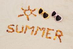 Μορφή του ήλιου και του καλοκαιριού λέξης με τα γυαλιά ηλίου στην άμμο στην παραλία, προστασία ήλιων, θερινός χρόνος Στοκ Εικόνα