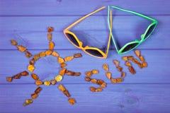 Μορφή του ήλιου με τον ήλιο λέξης φιαγμένη από ηλέκτρινα πέτρες και γυαλιά ηλίου, έννοια του θερινού χρόνου Στοκ εικόνες με δικαίωμα ελεύθερης χρήσης