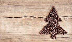Μορφή του χριστουγεννιάτικου δέντρου φιαγμένη από φασόλια καφέ στον ξύλινο πίνακα Στοκ εικόνες με δικαίωμα ελεύθερης χρήσης