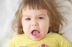 0 μορφασμός προσώπου μικρών κοριτσιών που βρίσκεται στο κρεβάτι που απομονώνεται Στοκ Φωτογραφίες