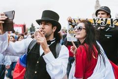 ΜΟΣΧΑ, ΡΩΣΙΑ - ΤΟΝ ΙΟΎΛΙΟ ΤΟΥ 2018: Ένας άνδρας σε ένα καπέλο σφαιριστών, το δεσμό τόξων και ένα κοστούμι φωτογράφισε τη ζώνη ανε στοκ φωτογραφία με δικαίωμα ελεύθερης χρήσης