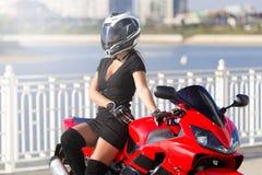 Μοτοσικλέτα, γυναίκα, μαύρο φόρεμα, μπότες, κράνος, τοποθέτηση Στοκ φωτογραφία με δικαίωμα ελεύθερης χρήσης
