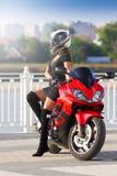 Μοτοσικλέτα, γυναίκα, μαύρο φόρεμα, μπότες, κράνος, τοποθέτηση Στοκ Εικόνες