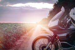 Μοτοσικλέτα περιπέτειας που στέκεται σε έναν βρώμικο δρόμο στο suset, απ στοκ εικόνες