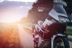 Μοτοσικλέτα περιπέτειας που στέκεται σε έναν βρώμικο δρόμο στο suset, απ στοκ φωτογραφίες