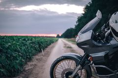 Μοτοσικλέτα περιπέτειας που στέκεται σε έναν βρώμικο δρόμο στο suset, απ στοκ εικόνα