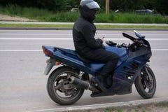 Μοτοσυκλετιστής που οδηγά στη μοτοσικλέτα του στο ηλιοβασίλεμα στοκ εικόνες