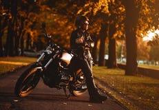 Μοτοσυκλετιστής με μια μοτοσικλέτα καφές-δρομέων Στοκ Φωτογραφία